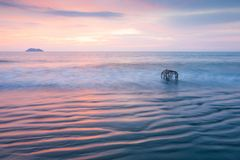 Beautiful gently waves, Ripple marks and traditional Thai fish t. Rap in surf in the ocean. Thailand. Slow shutter speed. Beautiful sunset and island background Royalty Free Stock Photos