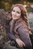 Beautiful genuine lady mystic with curly brunette hairs and adorable eyes dressed in fancy stylish warm clothes with fur on neck l. Onely posing sit for camera Royalty Free Stock Image