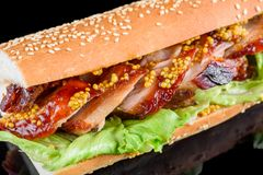 Giant BBQ Rib Sandwich with salad leaf and French mustard in baguette. isolated on a black background royalty free stock image