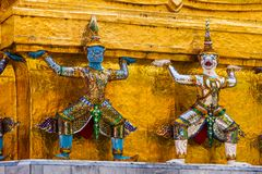 Giant statues at the base of Gold pagoda in Wat Pra Kaew in The Grand Palace royalty free stock photo