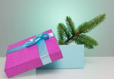 A beautiful gift box in blue, with a purple ribbon and bow. In it lies a branch of a Christmas tree. Beautiful Christmas Stock Photography