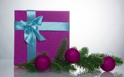 A beautiful gift box in blue, with a purple ribbon and bow. Next to it is a branch of a Christmas tree with Christmas Royalty Free Stock Photo