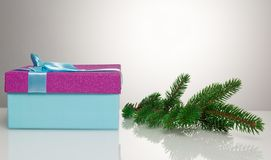 A beautiful gift box in blue, with a purple ribbon and bow. Next to it lies a branch of a Christmas tree. Beautiful Royalty Free Stock Image