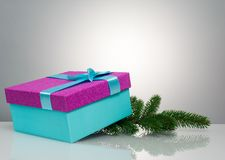 A beautiful gift box in blue, with a purple ribbon and bow. Under it lies a branch of a Christmas tree. Beautiful Royalty Free Stock Photography