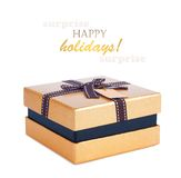 Beautiful gift box in gold paper with bow and label Royalty Free Stock Photos