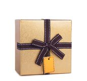 Beautiful gift box in gold paper with bow and label Royalty Free Stock Images