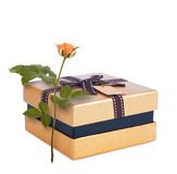 Beautiful gift box in gold paper with bow and rose Stock Photo