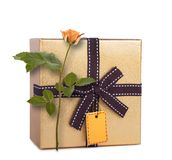 Beautiful gift box in gold paper with bow and rose Royalty Free Stock Photography