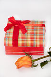 Beautiful gift box with red bow and orange rose Royalty Free Stock Photography