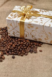 Beautiful gift box in roasted coffee beans on a brown jute backg. Round. Selective macro focus. Copy space Stock Photos