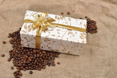 Beautiful gift box in roasted coffee beans on a brown jute backg. Round. Selective macro focus. Copy space Stock Photo