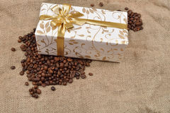 Beautiful gift box in roasted coffee beans on a brown jute backg. Round. Selective macro focus. Copy space Stock Images