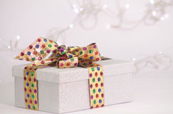 Beautiful gift box in shiny material with golden ribbon. And bow Stock Photography