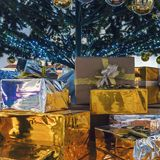 Beautiful gift boxes and blurred Christmas tree on background stock photography