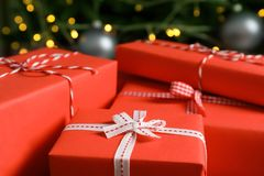 Beautiful gift boxes and blurred Christmas tree. On background Stock Images
