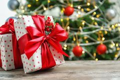 Beautiful gift boxes and blurred Christmas tree. On background Stock Photos