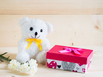 A beautiful gift with lovely bear and nice white carnation flower on wooden background Royalty Free Stock Images