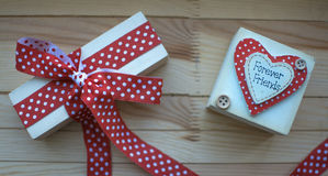 Beautiful gift with a red ribbon in polka dots and box Forever f. Beautiful gift with red ribbon in polka dots and box Forever friends on a wooden background Royalty Free Stock Photos