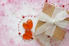 Beautiful gifts on a pink background of hearts bokeh. The concept of Valentine`s Day.Red heart with brown recycled gift box over w royalty free stock images