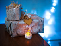 Beautiful gifts stand on  table beside a candle Royalty Free Stock Image