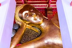 A beautiful gilded reclining Buddha image is located within the compound of Wat Pa Mok Worawihan, royalty free stock photo