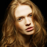 Beautiful ginger girl on black background Stock Photos