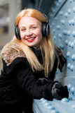 Beautiful ginger girl with headphones and black jacket Royalty Free Stock Photos