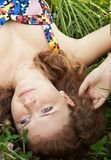 Beautiful ginger girl is lying in the green grass Stock Photography