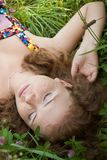 Beautiful ginger girl is lying in the green grass Royalty Free Stock Photos