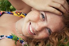Beautiful ginger girl is lying in the green grass Stock Photo