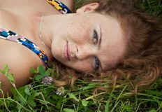 Beautiful ginger girl is lying in the green grass Stock Photos