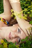 Beautiful ginger girl is lying in the green grass Stock Images