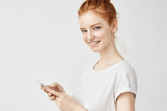 Beautiful ginger girl smiling holding phone twitting or using social media over white wall Royalty Free Stock Images