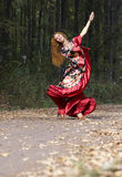 A beautiful ginger-haired girl. In gipsy suit dancing in fall royalty free stock images