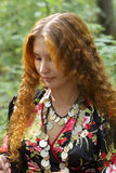 A beautiful ginger-haired girl. Walking in forest stock photography