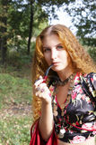 A beautiful ginger-haired girl in gipsy suit. With pipe stock photo
