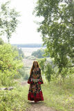 A beautiful ginger-haired girl in gipsy suit. On path in forest royalty free stock photos