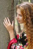 A beautiful ginger-haired girl in gipsy suit. Near a tree stock photography