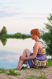 Beautiful ginger-haired woman at the coast of pond Stock Images