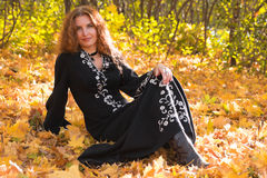 A beautiful ginger-haired woman in fall forest Stock Photography