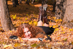 A beautiful ginger-haired woman in fall forest royalty free stock image