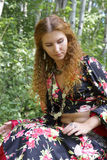 A beautiful ginger-haired woman in gipsy suit. Resting in forest stock images