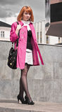 Beautiful ginger-haired woman in pink coat Stock Photo