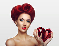 Beautiful ginger lady holding a crystal heart in hands Royalty Free Stock Image