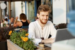 Beautiful ginger male freelancer with stylish haircut and beard smiles, looking at camera and working on laptop computer Royalty Free Stock Photos