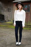 Beautiful Ginger Teenager In Front Of Stables. Portrait of a beautiful ginger teenage girl wearing a hat, white shirt with a pearl collar  black trousers and Royalty Free Stock Photography