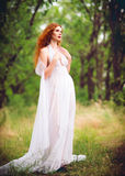 Beautiful ginger woman wearing white dress in a garden Stock Image