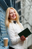 Beautiful ginger woman in white shirt holding note-book. Standing next blue wall Stock Image