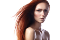 Beautiful ginger young woman with flying hair and naturel makeup. Beauty portrait of sexy model with straight red hair Royalty Free Stock Photo
