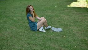 Beautiful ginger young woman talking on phone and laughing, sitting on grass, happy and cheerful female speaking stock video footage